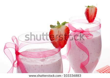 Delicious fruit milkshake detail decorated with pink ribbon and strawberry isolated on white background. - stock photo