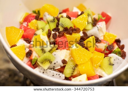 Delicious Fruit Salad with watermelon, oranges, kiwi and raisins - stock photo