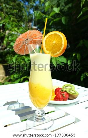 Delicious fruit smoothie on white table, outdoors - stock photo