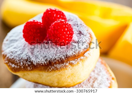 delicious german doughnuts powdered with sugar and raspberry on the top - stock photo
