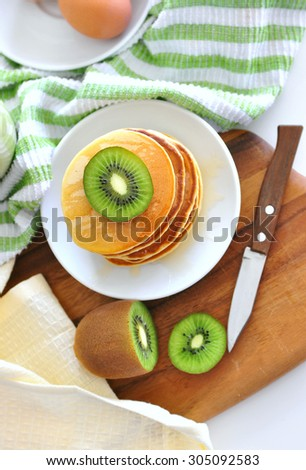 Delicious golden pancakes cooked on dry pan and served for breakfast with honey and kiwi fruit on a wooden board. Healthy eating lifestyle, still life, copy space, top view on the table - stock photo