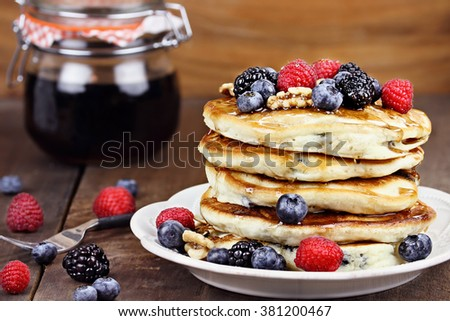Delicious golden pancakes with fresh blackberries, raspberries, blueberries and sweet maple syrup. Extreme shallow depth of field. - stock photo