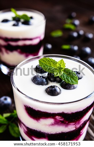 Delicious Greek yogurt with fresh blueberries in a glass jar on a wooden background - stock photo