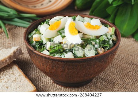 Delicious green spring salad with chopped garlic and ramson served in rustic bowl on vintage wooden background - stock photo