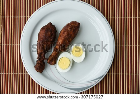 Delicious Grilled chicken legs with eggs served on a white plate on a bamboo mat background. Tasty Roasted chicken drumstick with boiled egg halves.chicken fry and egg white, yolk of egg - stock photo