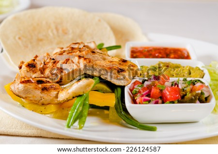 Delicious grilled chicken with a selection of sauces and vegetable accompaniments, spicy hot chili salsa and corn tortillas served on a plate - stock photo
