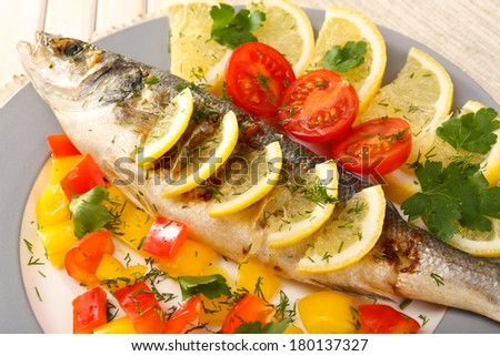 Delicious grilled fish on plate on table close-up - stock photo