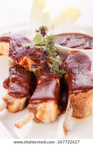 Delicious grilled pork ribs served with a rich brown gravy or BBQ sauce garnished with fresh herbs , close up side view - stock photo