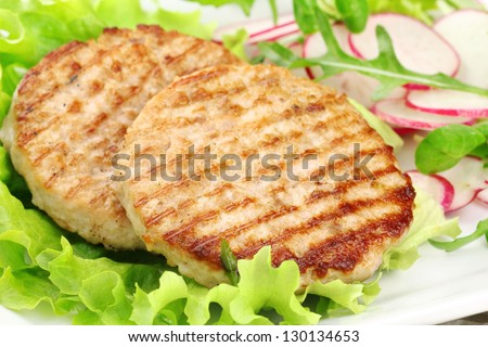 Delicious grilled rabbit burgers served with fresh salad and radish - stock photo