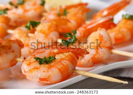 Delicious grilled shrimp on wooden skewers on a plate macro. horizontal  - stock photo
