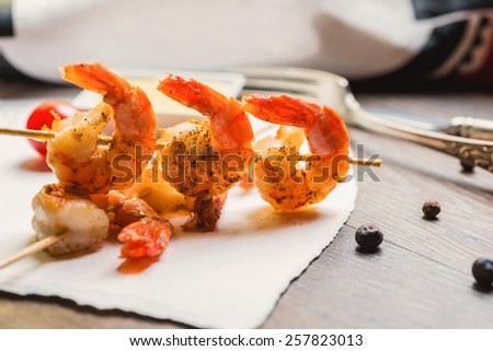 Delicious grilled shrimp on wooden skewers with sauce on a wooden table - stock photo