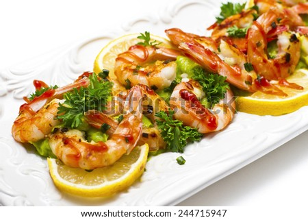 Delicious grilled shrimps with guacamole and herbs on the white plate - stock photo