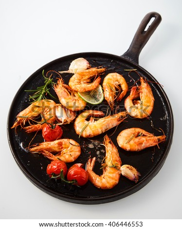 Delicious grilled spicy prawns seasoned with rosemary, fresh garlic, lime and cherry tomatoes viewed from overhead in an old rustic frying pan on white - stock photo