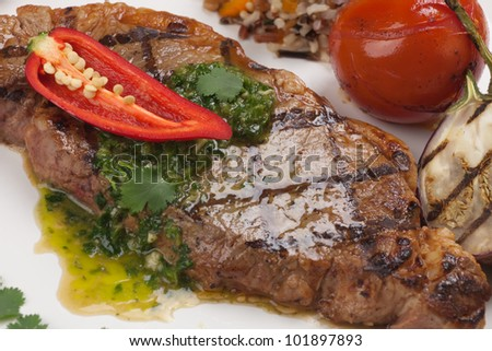 Delicious grilled steak with spicy herb sauce, garnished with grilled vegetables and organic brown rice. - stock photo