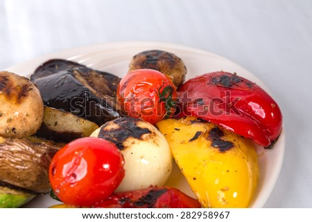 Delicious grilled vegetables. Macro. Plate located on a white canvas tablecloth background. - stock photo