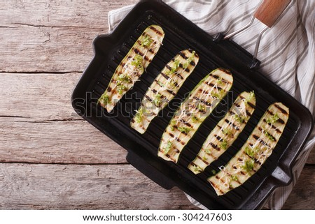 Delicious grilled zucchini with cheese on a grill pan close-up. horizontal view from above - stock photo