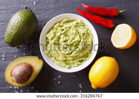 Delicious guacamole sauce and ingredients on the table. Horizontal top view - stock photo