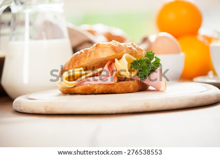 Delicious ham and cheese croissant on a wooden table - stock photo