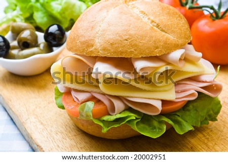 Delicious ham, cheese and salad sandwich with olives - stock photo