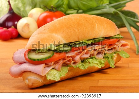 Delicious ham, cheese and salad sandwiches on a wooden board - stock photo