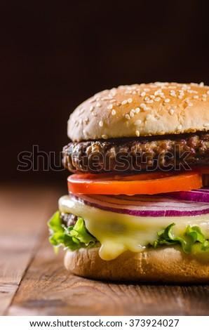 Delicious hamburger on dark wooden background - close-up - stock photo