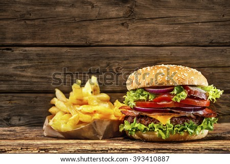 Delicious hamburger with french fries on wooden table - stock photo