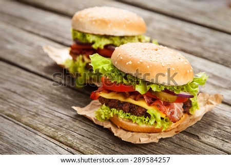 Delicious hamburgers on wooden background - stock photo