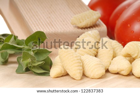 Delicious hand made Gnocchi using a Gnocchi board with tomatoes and herbs - stock photo