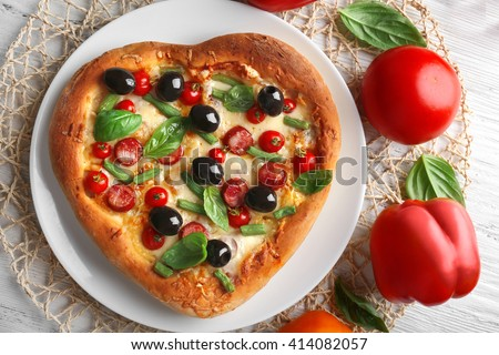 Delicious heart shaped pizza on the plate with vegetables around, close up - stock photo