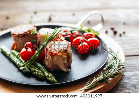 Delicious holiday dinner on a wooden table. Tasty holiday meat with fresh vegetables. Dinner in restaurant of mediterranean cuisine  - stock photo