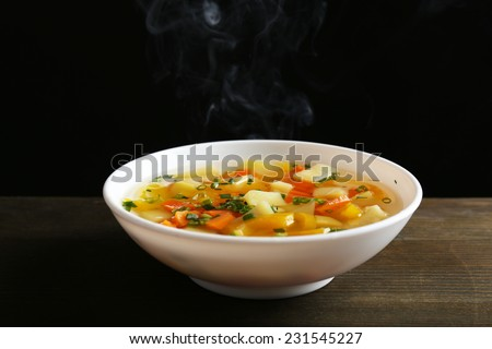 Delicious home cooked food with steam on table on black background - stock photo