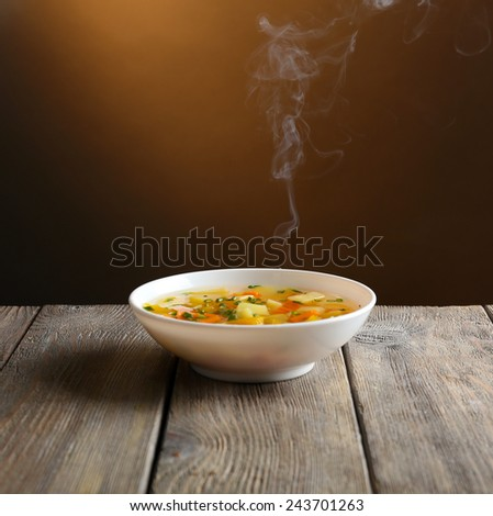 Delicious home cooked food with steam on table on brown background - stock photo