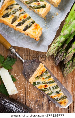 Delicious home made asparagus savory tart with pecorino and bacon on old wooden background.  Selective focus. Top view. - stock photo