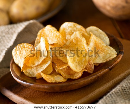 Delicious home made potato chips with sea salt and black pepper against a rustic background. - stock photo