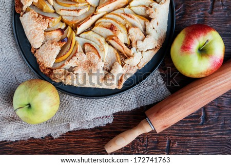 Delicious homemade apple pie, rolling-pin and apples - stock photo