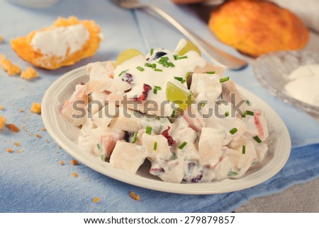 Delicious homemade chicken salad with yogurt, grapes, apples and cranberries on white plate with carrot buns on blue background, Selective focus.  Healthy eating. Toned - stock photo