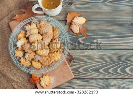 Delicious homemade cookies in the form of a maple leaf, oak leaves, acorns and hedgehog on wooden background. - stock photo