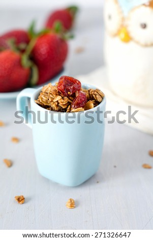 Delicious homemade granola with dried fruits in blue cup. Fresh strawberries and owl cup on background - stock photo
