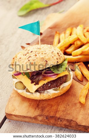 Delicious homemade hamburger with french fries on wooden vintage table - stock photo