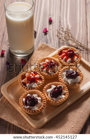 Delicious homemade mini berry tarts and custard on wood cutting board - stock photo
