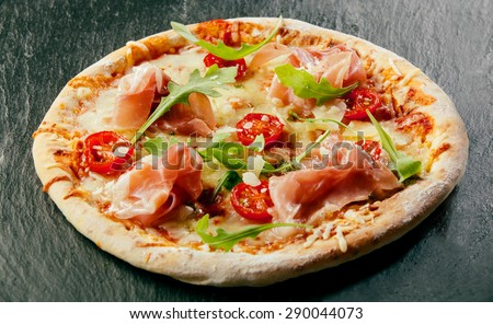 Delicious homemade pizza with a thick base or crust topped with mozzarella cheese, tomato paste, ham and fresh rocket leaves on a black counter top - stock photo