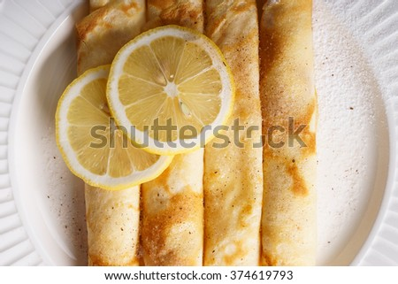 delicious homemade rolled pancakes with fresh lemon  - stock photo