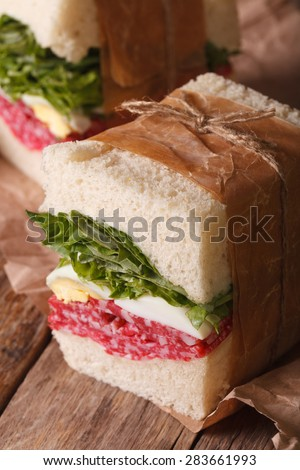 delicious homemade sandwich with salami and egg wrapped in paper close-up on the table. vertical - stock photo