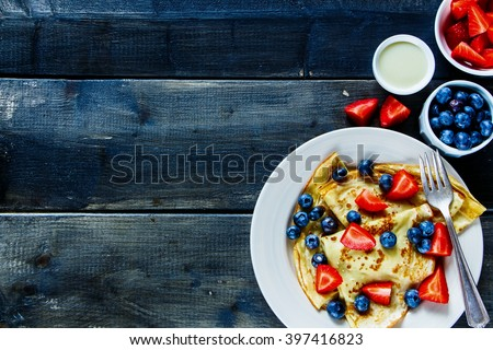 Delicious homemade thin pancakes or crepes with fresh berries and cream on plate over rustic wooden background, top view, free text space. - stock photo