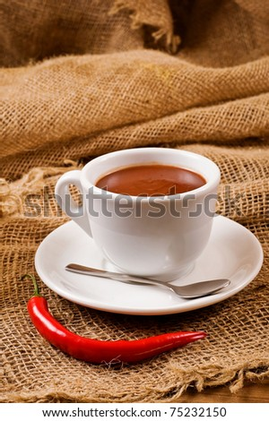 Delicious hot chocolate in a white mug with chilly pepper. Shallow depth of field. - stock photo