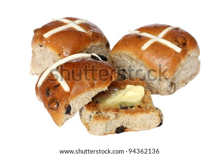 Delicious hot cross buns, one toasted with butter, isolated on white. - stock photo