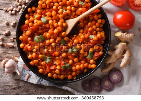 Delicious Indian cuisine: Chana masala with ingredients close-up on the table. horizontal top view - stock photo