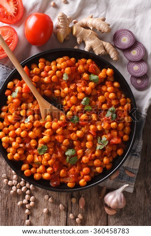 Delicious Indian cuisine: Chana masala with ingredients close-up on the table. Vertical top view - stock photo