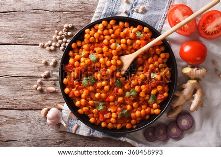 Delicious Indian cuisine: Chana masala with ingredients on the table. Horizontal top view - stock photo