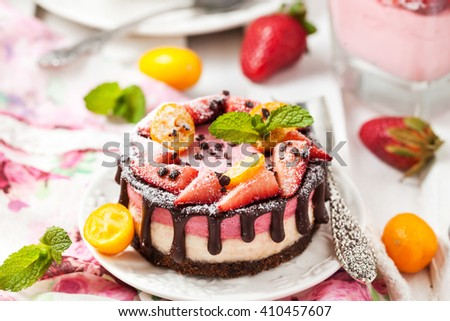 Delicious individual mini cake (cheesecake) decorated with chocolate and strawberry - stock photo
